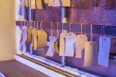 brown paper labels tied to window bars with names of prisoners detailed